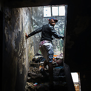 """Simo on his way up to the roof a """"hijacked building"""" (illegally occupied squat) he lives in in Hillbrow, one of Johannesburg, South Africa's most notorious neighbourhoods. The building has neither electricity nor running water, and refuse is piled up outside the walls. Simo says he has been living here for 16 years."""
