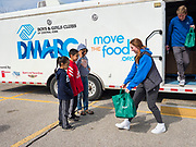 """17 MARCH 2020 - DES MOINES, IOWA:  SARAH MERCER-SMITH (center) and GRADY FOX (right) both with the Boys & Girls Clubs and working with the Des Moines Area Religious Council (DMARC) brings bags of food to a family in the parking lot of Carver Elementary School in Des Moines after giving bags of food to a family. Des Moines Public Schools are closed for at least 30 days because of the Coronavirus outbreak. Des Moines area religious organizations and food banks are working together to bring free food to children in at risk communities. Volunteers and workers are practicing """"social distancing"""" by leaving the food packages on the pavement and recipients pick up the packages. Tuesday, the Governor of Iowa ordered all restaurants and bars to close or go to take out only. The Iowa Department of Public Health has urged all public buildings, like libraries and schools, to close, and all schools in Iowa are closed for at least 30 days.  PHOTO BY JACK KURTZ"""