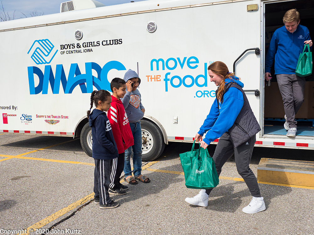 "17 MARCH 2020 - DES MOINES, IOWA:  SARAH MERCER-SMITH (center) and GRADY FOX (right) both with the Boys & Girls Clubs and working with the Des Moines Area Religious Council (DMARC) brings bags of food to a family in the parking lot of Carver Elementary School in Des Moines after giving bags of food to a family. Des Moines Public Schools are closed for at least 30 days because of the Coronavirus outbreak. Des Moines area religious organizations and food banks are working together to bring free food to children in at risk communities. Volunteers and workers are practicing ""social distancing"" by leaving the food packages on the pavement and recipients pick up the packages. Tuesday, the Governor of Iowa ordered all restaurants and bars to close or go to take out only. The Iowa Department of Public Health has urged all public buildings, like libraries and schools, to close, and all schools in Iowa are closed for at least 30 days.  PHOTO BY JACK KURTZ"