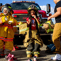 Eialyah Dilyou, left, and Daysha Willie try on firefighter gear from the White Cliffs volunteer fire department during the National Night Out event at the Rio West Mall in Gallup Tuesday.