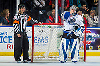KELOWNA, CANADA - OCTOBER 5:  Referee Chris Crich stands at the net of Griffen Outhouse #30 of the Victoria Royals against the Kelowna Rockets on October 5, 2018 at Prospera Place in Kelowna, British Columbia, Canada.  (Photo by Marissa Baecker/Shoot the Breeze)  *** Local Caption ***
