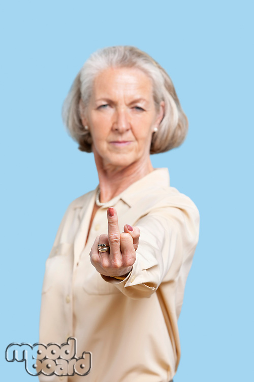 Portrait of senior woman in casuals making rebellious gesture against blue background