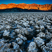 Sunset over the peaks of Death Valley with salt formations of Badwater.