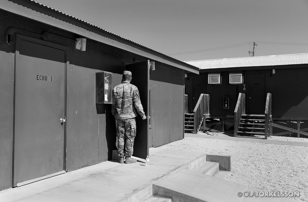 A military guard at the prison camp at Guantanamo, Cuba, Jan 28 2017, guards a door to a room where the prisoners can meet and talk with their lawyers.<br /> The guards turn away their faces so you cannot identify them. It is standard operation procedure when pictures are made. When you work as a journalist at the Guantanamo you work under military censorship and all your material is checked every day and approved for publication.<br /> The prison camp on the Guant&aacute;namo naval base was the creation of President George W. Bush. The prison camp was considered an important part of the US war on terrorism. Over the years, 779 people have been brought to the camp. 41 people are still detained. Of them, 26 people count as &quot;forever prisoners&rdquo;, indefinite detainees under the Law of War. Two prisoners have been in the camp since it was opened in January 2002. The last prisoner taken to the camp came in March 2008. The so-called war on Terror and the Guantanamo prison camp have been heavily criticized for violation of human rights regarding torture and habeas corpus.<br /> It is unclear what US President Donald Trump wants to do with the camp, but during the election campaign he said that he would fill Guant&aacute;namo Bay with &quot;bad dudes&quot;. Photo by Ola Torkelsson<br />