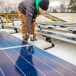 A PV Squared employee (Evan Dick) installing solar panels on the roof of a commercial building in Greenfield, Massachusetts.