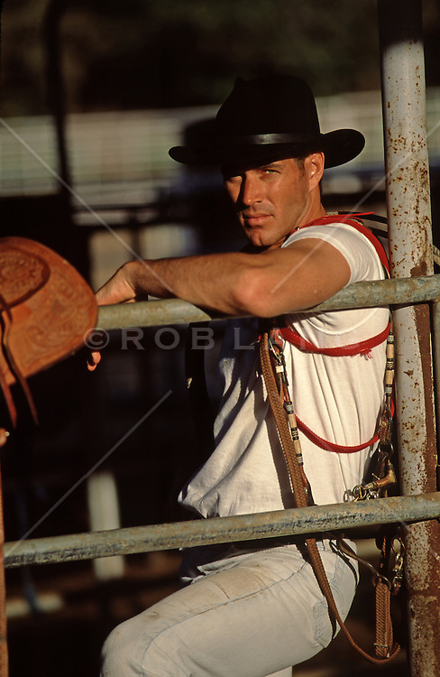 hot cowboy leaning on a fence