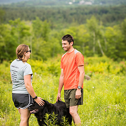 A man and woman trail running with their dogs in the new Bethel Community Forest in Bethel, Maine.
