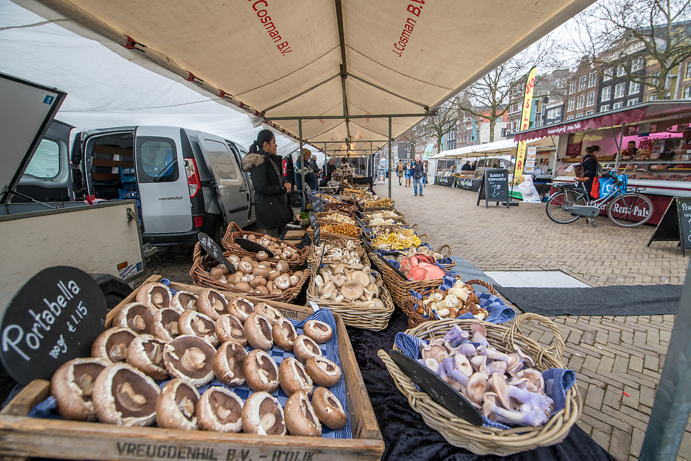 Rows of mushrooms rest on a table in a market in Amsterdam, Netherlands