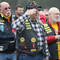 Joe Crisler salutes during the National Anthem at the replica of the Vietnam Wall.  Crisler is a member of the In Country Vietnam Motorcycle Club and road with the Patriot Guard to Veterans park