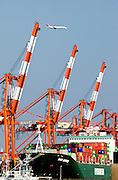 A Japan Airlines plane flies over cranes used for loading cargo onto ships in Tokyo Bay, Tokyo, Japan.