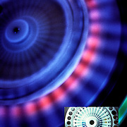 Looking down at a centrifuge testing the samples at a very high speed using a blue light to show the separation.<br />