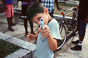 A boy in Havana, Cuba plays with a toy gun.