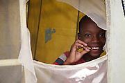 Port-au-Prince, Cite? Soleil..camp de re?fugie?s de Parc Couronne,.Me?decins du Monde, clinique mobile..Port-au-Prince, Hai?ti. A? l'inte?rieur d'une clinique mobile installe?e par «Me?decins du Monde» dans le quartier de Cite? Soleil. Je photographie les gens qui viennent pour une consultation et la distribution de me?dicaments afin de contrer la vague re?cente de chole?ra lorsque je me retourne et vois ce jeune garc?on m'observant par la fene?tre de la clinique..
