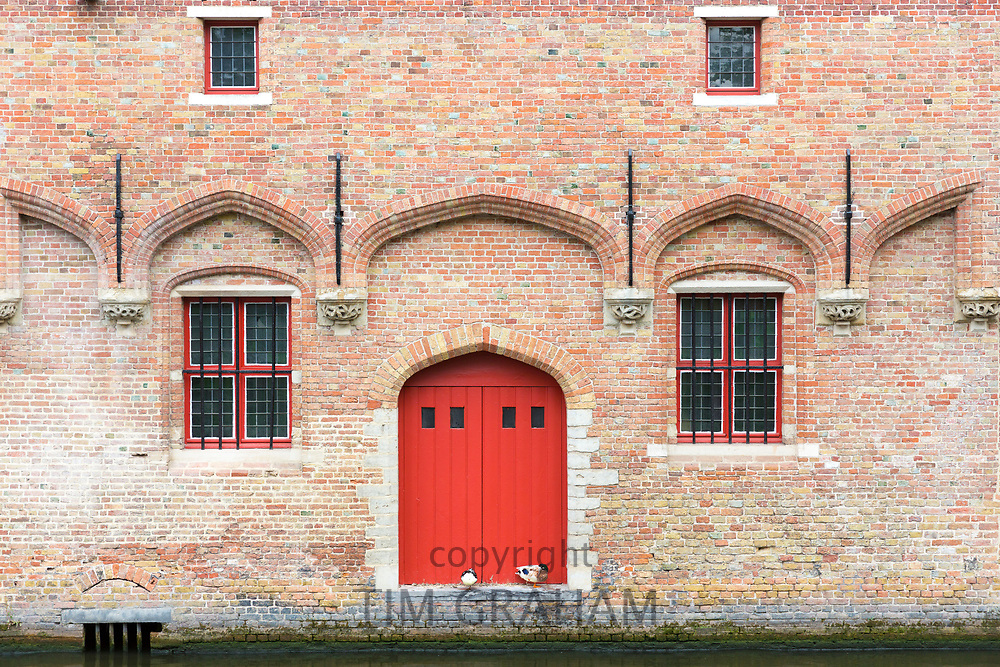Traditional door and doorway of almshouses, beside Groenerei (Green Canal) painted bright red, old town Bruges, Belgium