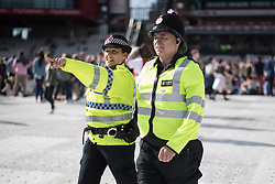 © Licensed to London News Pictures . 04/06/2017 . Manchester , UK .  Police inside the stadium as the crowd gathers in front of the stage . The One Love Manchester benefit concert for victims of the Manchester Arena terrorist attack , at the Emirates Old Trafford Cricket Stadium . Ariana Grande, Justin Bieber, Coldplay, Katy Perry, Miley Cyrus, Pharrell Williams, Usher, Take That, Robbie Williams, Black Eyed Peas and Niall Horan are amongst the performers . Photo credit : Joel Goodman/LNP