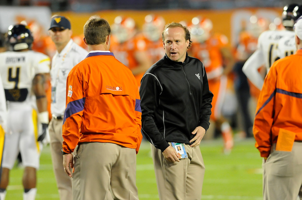 January 4, 2012: Head coach Dana Holgorson of West Virginia chats with head coach Dabo Swinney of Clemson before the NCAA football game between the West Virginia Mountaineers and the Clemson Tigers at the 2012 Discover Orange Bowl at Sun Life Stadium in Miami Gardens, Florida.