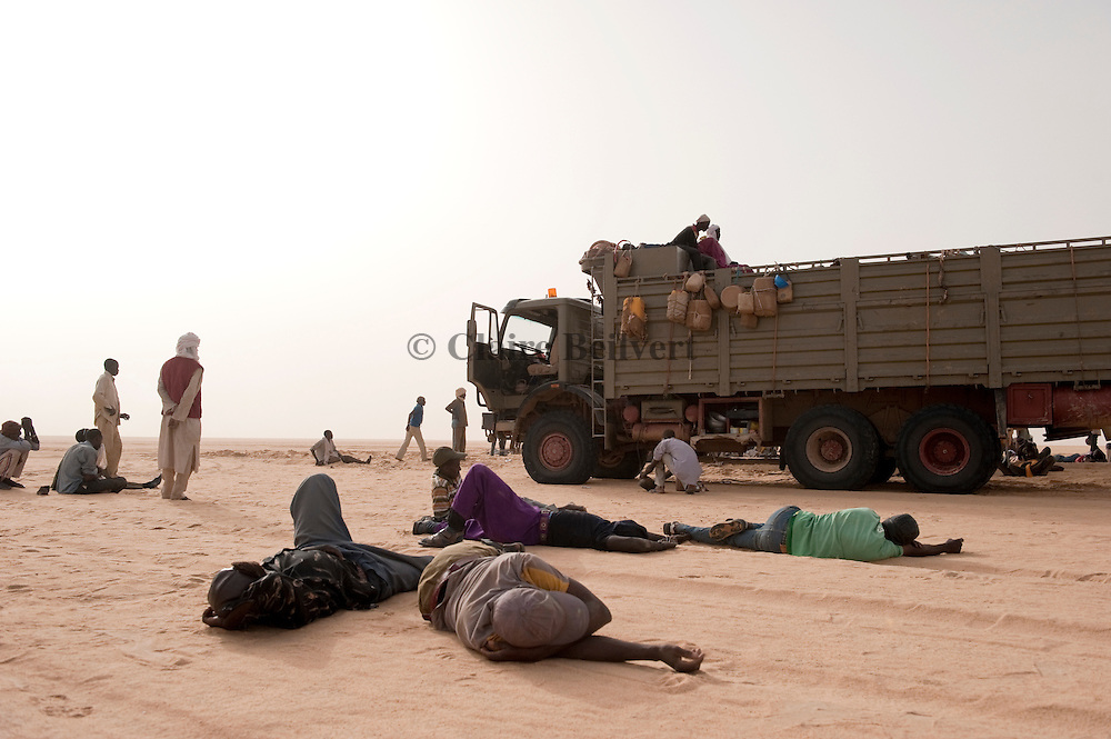 Bivouac in the ténéré desert. The truck drivers have stopped after a long night drive. The iillegal passengers, all migrants from Africa are exhausted, some are sleeping on the sand, near the trucks.