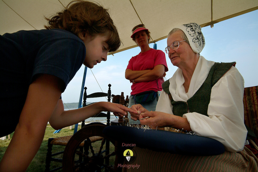"August 25, 2007 -- PHIPPSBURG, Maine.  Lynne White, sitting, of West Springfield, Mass., works on a piece of Bobbin Lace with Jessica Strack, 9, of Reading, Mass. at the celebration of the 400th anniversary of the Popham Colony on Saturday as Jessica's mother, Norma, looks on. Jessica made this piece of lace and was ready to keep it going.  ""Jessica could do this herself anytime,"" said White, ""She came back 2 days in a row and was ready to finish what she started yesterday,"" said White. ""And she did a great job!"" .White is a member of The Society of the 17th Century, an organization of 17th and 18th Century re-enactors. The group set up at Popham in order to provide a sense of what life might have been like in the Popham Colony -- which was founded in 1607 in present day Phippsburg. While the colony lasted less than a year, it was one of the first steps towards establishing permanent settlements of Europeans in North America. Photo by Roger S. Duncan."