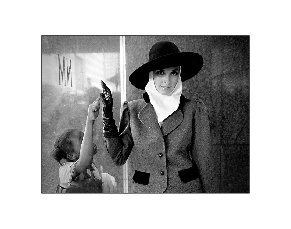 In the early 1980's...A high fashion model poses during a fashion shoot at the Neiman Marcus store in Dallas, Texas, as a young passer-by attempts to make contact by pressing her hand to the glass.  ©Ed Hille