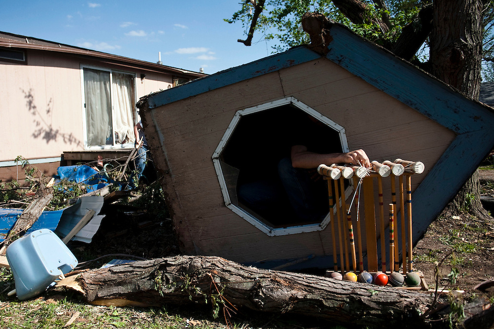 Lincoln, Neb.-05/19/2014-James Upton, 25, removes the entertainment items from a play house in front of his home a week after the tornado hit Beaver Crossing Monday, May 19, 2014.<br />