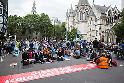 London, UK. 15 July, 2019. Climate activists from Extinction Rebellion block the road outside the Royal Courts of Justice, with a boat named the Polly Higgins after the barrister who fought for legal recognition of ecocide acting as a focal point for their protest,  at the beginning of the group's 'summer uprising', a series of events intended to apply pressure on local and central government to address the climate and biodiversity crisis. Credit: Mark Kerrison/Alamy Live News
