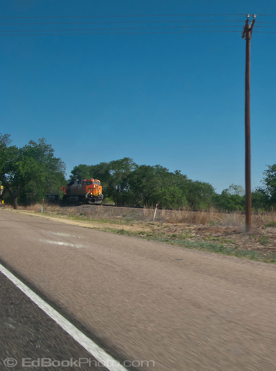A BNSF (Burlington Northern Santa Fe) railroad freight train passes by along rural I-20 in west Texas, USA
