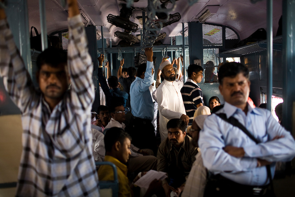 Men crowd in to a commuter train leading from the poor suburbs to downtown Mumbai.  Crowded environments are one of the risk factors in concentrated urban environments, making it much easier for TB to be passed from one person to another.  It is estimated that nearly 1 in 3 people in India are infected with the bacteria that can cause active TB.