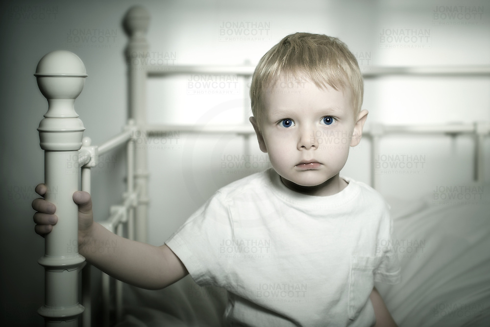 Portrait of 3 year old boy sitting on his bed. He gazes into the camera and we interpret the look. Is he thoughtful, pensive, fragile, vulnerable? Or all of them? This look can encompass many different moods and feelings.