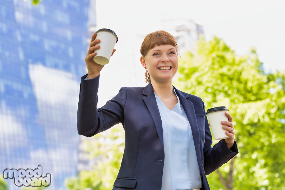 Young beautiful businesswoman holding two cups of coffee