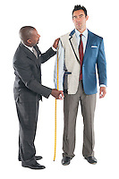 Man getting measured by a tailor on a white background