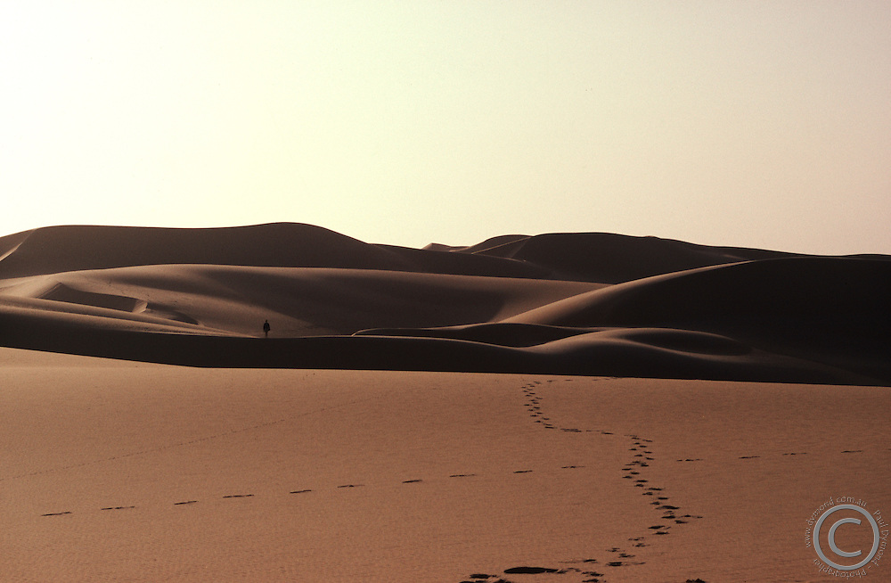 A lone man wanders through the Saraha Desert on the outskirts of Chinguetti, Mauritania, north Africa