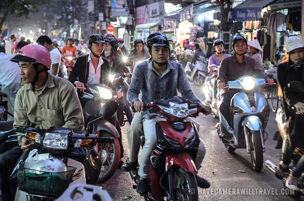 Scooters crowd the roads of Hanoi's Old Quarter at night.