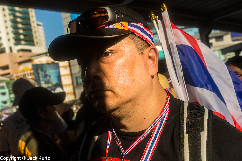 """13 JANUARY 2014 - BANGKOK, THAILAND: An anti-government protestors walks through the skywalk in the Asok intersection in Bangkok. Tens of thousands of Thai anti-government protestors took to the streets of Bangkok Monday to shut down the Thai capitol. The protest was called """"Shutdown Bangkok"""" and is expected to last at least a week. The Shutdown Bangkok protest is a continuation of protests that started in early November. There have been shootings almost every night at different protests sites around Bangkok, including two Sunday night, but the protests Monday were peaceful. The malls in Bangkok stayed open Monday but many other businesses closed for the day and mass transit was swamped with both protestors and people who had to use mass transit because the roads were blocked.    PHOTO BY JACK KURTZ"""