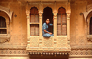 INDIA, RAJASTHAN a girl in the carved window of her home in the ancient city of Jaisalmer, in the  Great Thar Desert