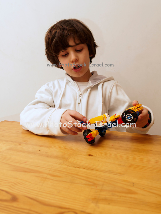 Young boy of seven plays with a transformer robot of building blocks