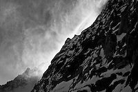 Spindrift cascades down a rock face along the Haute Route, Switzerland.
