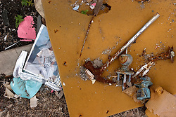 10 December, 05.  New Orleans, Louisiana. Post Katrina aftermath. <br />  Gentilly. A smashed photo frame and a discarded survivor's hammer used to smash through an attic to freedom during the storm.<br /> Photo; &copy;Charlie Varley/varleypix.com