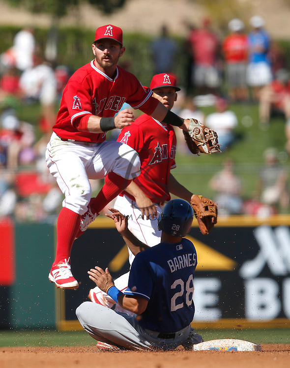 Mar 9, 2016; Tempe, AZ, USA; Los Angeles Angels second baseman Johnny Giavotella (12) turns the double play while avoiding Los Angeles Dodgers catcher Austin Barnes (28) in the fourth inning during a spring training game at Tempe Diablo Stadium. Mandatory Credit: Rick Scuteri-USA TODAY Sports
