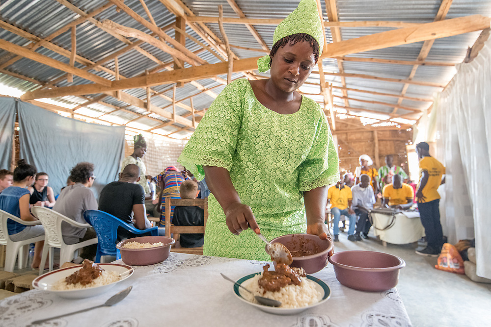 A woman in a colorful dress serves food onto plates in Ganta, Liberia.