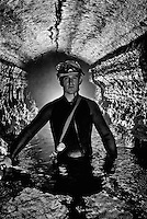 Using a electronic flash in front and back, a caver pauses in a watery passage.