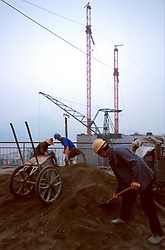 CHINA HUBEI PROVINCE THREE GORGES DAM MAY99 -- Workers shovel cement at the construction site of the Three Gorges Dam. Seven large cities, including Chongquing, and thousands of villages will be submerged once the water level rises after the completion of the controversial Three Gorges Dam project further downriver. The flooding of areas reaching back more than 550Km upriver will require the evacuation and resettlement of more than 10 million people.  jre/Photo by Jiri Rezac. . © Jiri Rezac 1999. . Contact: +44 (0) 7050 110 417. Mobile:  +44 (0) 7801 337 683. Office:  +44 (0) 20 8968 9635. . Email:   jiri@jirirezac.com. Web:     www.jirirezac.com