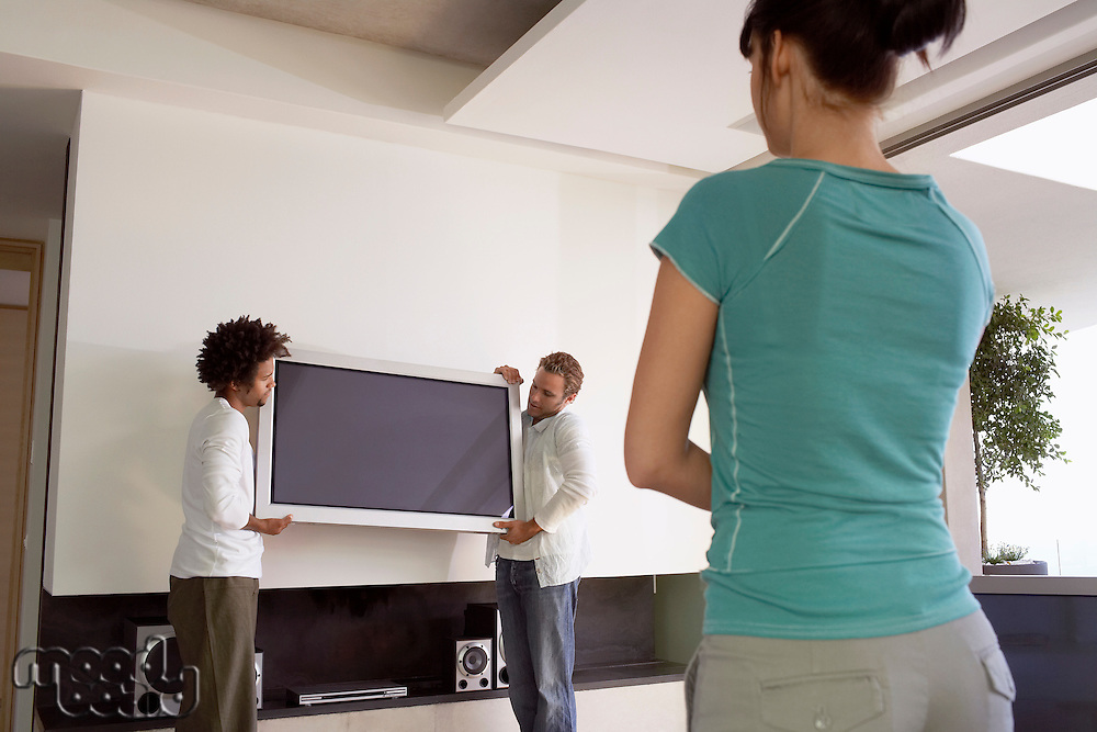 Young woman watching as two young men move plasma television back view