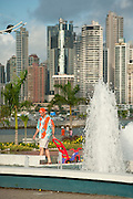 Man at fountain and Punta Paitilla condominiums on background. Cinta Costera bayside road, Panama City, Panama, Central America.