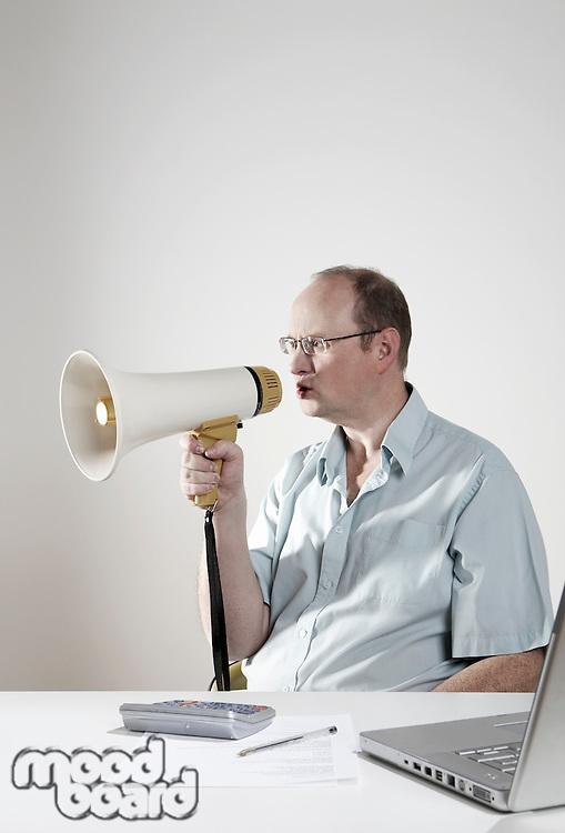 Businessman sitting at desk talking through megaphone