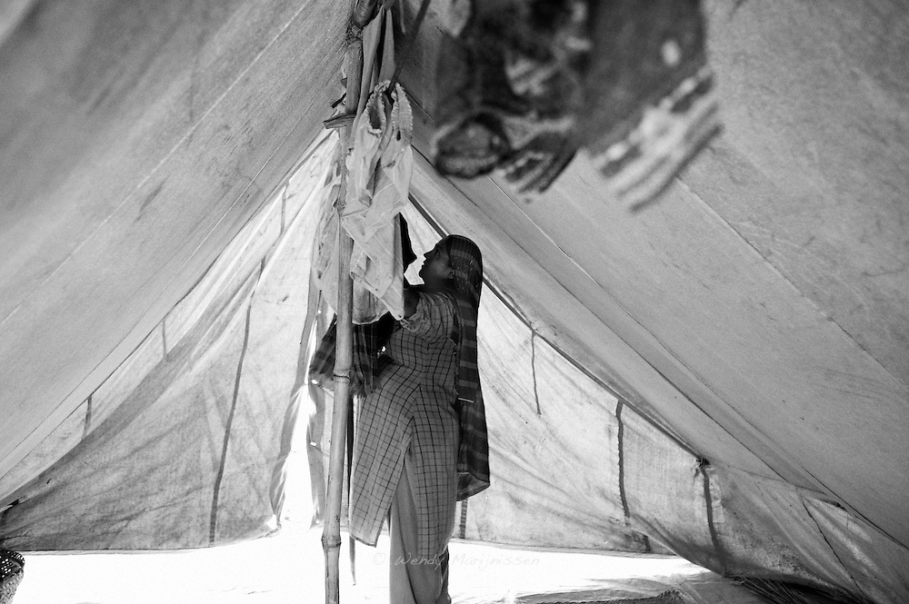 A pregnant woman in labor about to go to the hospital to give birth, is hanging up the washed clothes of her other children. Living in the camp makes conditions for pregnant women even harder. Most women are anemic and complain of the heat of living in the tents. Keamari town, Karachi, Pakistan, 2010