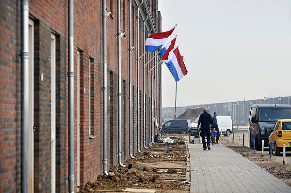 Nederland, Nijmegen, 8-9-2011Bouwvakkers zijn bezig met het bouwen van huizen in de nieuwe wijk Laauwik, onderdeel van de stadsuitbreiding van Nijmegen in Lent. Bij pas opgeleverde huizen hangt de nederlandse vlag uit.Foto: Flip Franssen/Hollandse Hoogte