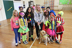 Visually impaired woman with guide dog with pupils at a primary school.