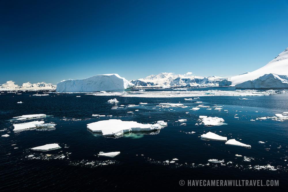 Scenic landscape on the Antarctic Peninsula, with small blocks of ice floating on the water in the foreground and ice in the background.