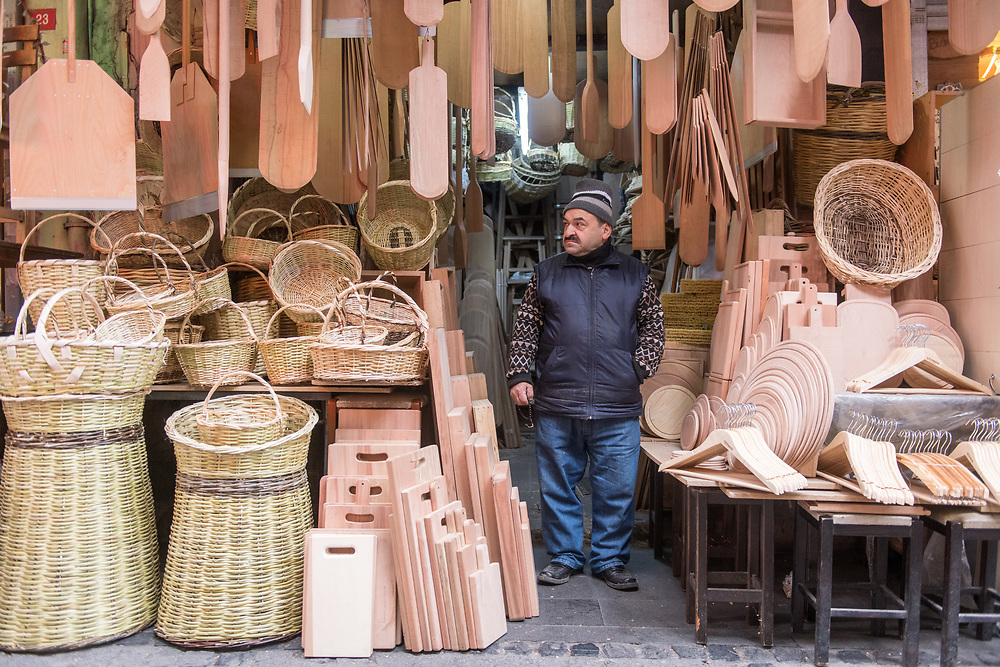 Adult male merchant stands with his hands in his pockets in entryway to shop that is selling wooden goods and woven baskets, Istanbul, Turkey.