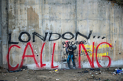 """© Licensed to London News Pictures. 23/01/2016. Calais, France. A defaced Banksy artwork surrounded by graffiti reading """"LONODN CALLING""""  at the entrance to the camp known as the 'Jungle' in Calais, France, where thousands of migrants and refugees attempting to reach the UK are currently living. Photo credit: Ben Cawthra/LNP"""